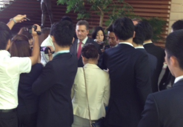 Jim DeMint, center, speaks with press in Tokyo yesterday.