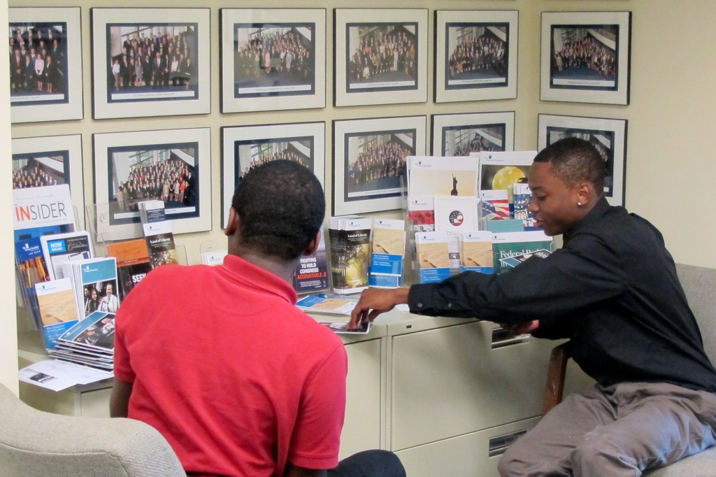 Denzel and James help to organize YLP brochures.