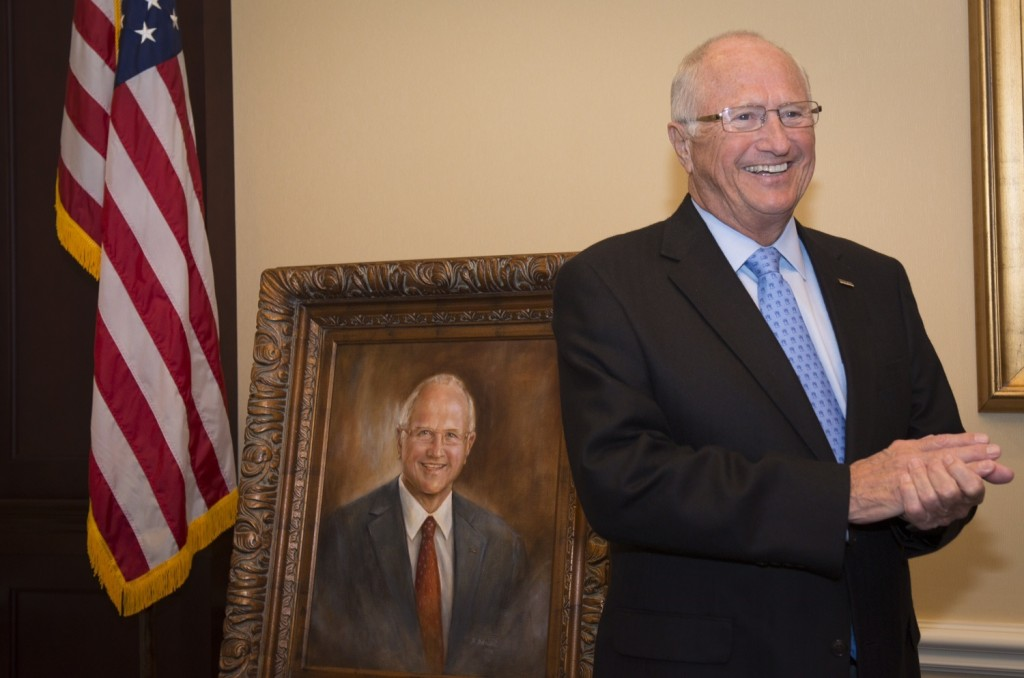 Heritage member Thomas Colbert poses with a portrait honoring his generosity.